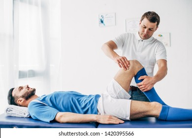 handsome Physiotherapist massaging leg of football player in hospital