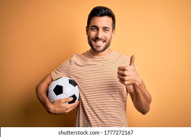 Handsome player man with beard playing soccer holding footballl ball over yellow background doing happy thumbs up gesture with hand. Approving expression looking at the camera showing success.
