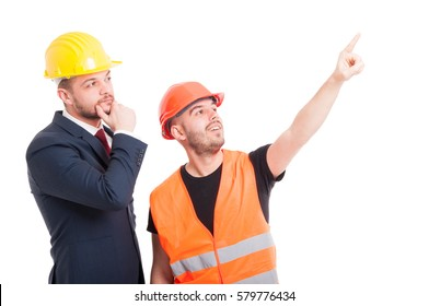 Handsome constructor pointing finger up and showing something to businessman on white background