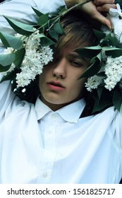 handsome portrait of a model guy in a white shirt in blooming white greens flowers with a cool look