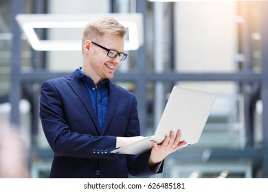 Handsome positive young German businessman in modern office. Portrait of business man in the hall of contemporary business office