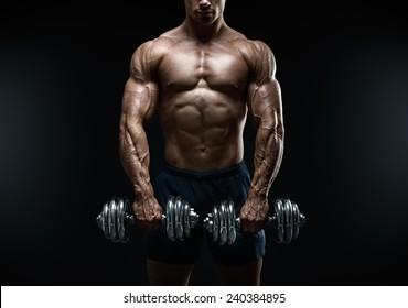 Handsome power athletic guy bodybuilder doing exercises with dumbbell. Fitness muscular body on dark background.