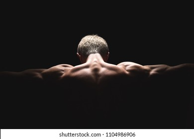 Handsome power athletic man in dramatic light. Strong bodybuilder with perfect shoulders, biceps, triceps, back, delta and chest. Strength and motivation. Bottom view