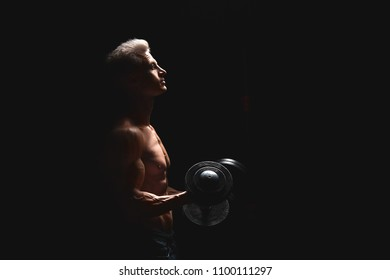 Handsome power athletic man with dumbbell confidently looking forward in dramatic light. Strong bodybuilder with six pack, perfect abs, shoulders, biceps, triceps and chest. Strength and motivation