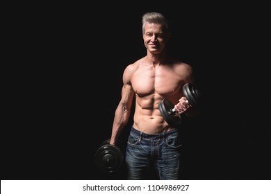 Handsome power athletic man with dumbbell confidently looking forward. Strong bodybuilder with six pack, perfect abs, shoulders, biceps, triceps and chest. Strength and motivation