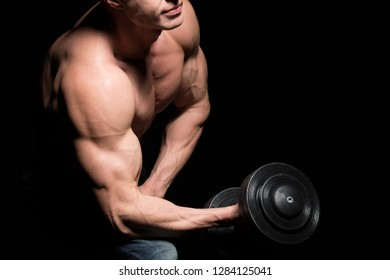 Handsome power athletic man with dumbbell. Strong bodybuilder with perfect shoulders and biceps. Strength and motivation