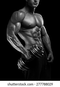 Handsome power athletic man with dumbbell. Strong bodybuilder with six pack, perfect abs, shoulders, biceps, triceps and chest. Black and white photo.
