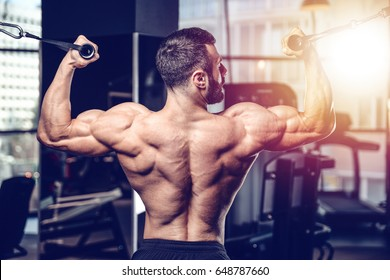 Handsome power athletic man on diet training pumping up back muscles pull up. Strong bodybuilder with six pack, perfect abs, back, shoulders, biceps, triceps and chest