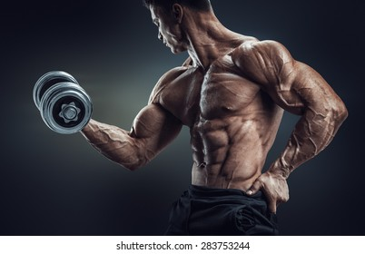 Handsome power athletic man in training pumping up muscles with dumbbell. Strong bodybuilder with six pack, perfect abs, shoulders, biceps, triceps and chest. Image with clipping path