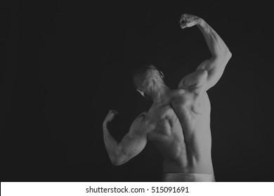 Handsome power athletic man in training pumping up muscles with dumbbell