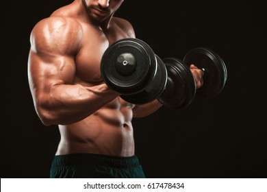 Handsome power athletic man in training pumping up muscles with dumbbells in a gym. Fitness muscular body isolated on dark background.