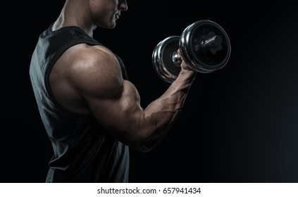 Handsome power athletic man in training pumping up muscles with dumbbell. Strong bodybuilder with perfect biceps curl, triceps and chest. Close-up of a power fitness man.