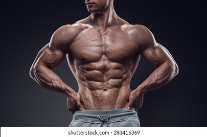 Handsome power athletic young man with great physique. Strong bodybuilder with six pack, perfect abs, shoulders, biceps, triceps and chest. Image have clipping path