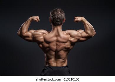 Handsome power bodybuilder showing his back