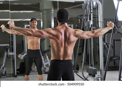 Handsome powerful athletic man doing cable crossover exercise. Strong bodybuilder with perfect abs, back and chest.
