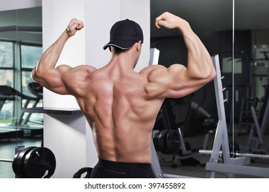 Handsome powerful athletic man posing at the gym. Strong bodybuilder with perfect muscular back, shoulders and biceps.
