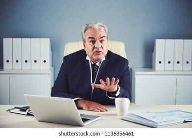 Handsome powerful senior male in dark elegant business suit sitting at office workplace and looking at camera being in control of situation and calming down someone's anger gesturing palm down.