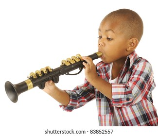 A handsome preschooler blowing his toy clarinet.  Isolated on white.