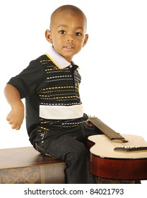A handsome preschooler happily playing guitar on a white background.