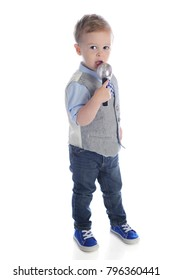 A handsome preschooler standing as he speaks or sings into a closely held microphone.  On a white background.