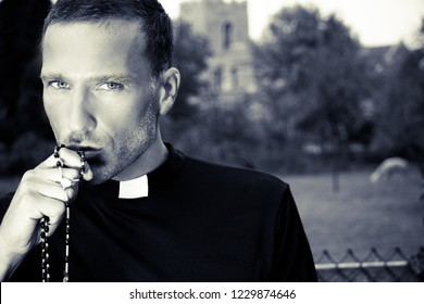 Handsome priest kissing his rosary in front of field with alpaca and church in background
