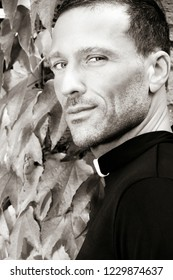 Handsome priest looks over his shoulder at camera with virginia creeper ivy in background