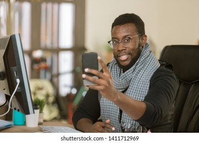 Handsome professional man in a creative office using his mobile device