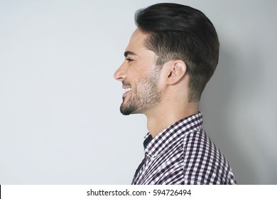 Handsome profile portrait of young man. Lovely appearance side look of smiled dark haired man in plaid shirt against light gray wall