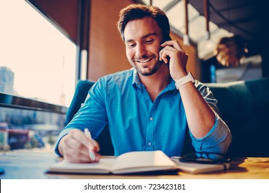 Handsome prosperous businessman noting contact while talking on mobile with assistant on break in cafe.Smiling manager discussing creative idea with partner making planning checklist in coffee shop