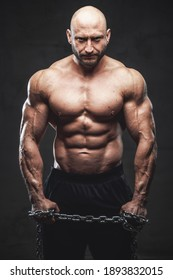 Handsome and proud man with muscular build and bald head poses with naked torso and steel chains in dark background looking at camera.