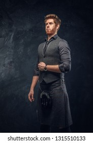 Handsome redhead man dressed in an elegant vest with tie and kilt in studio against a dark textured wall