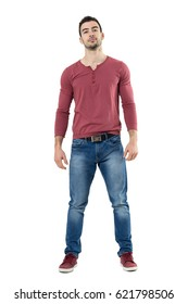 Handsome relaxed male fashion model wearing jeans and red v-neck shirt looking at camera. Full body length portrait isolated over white background.