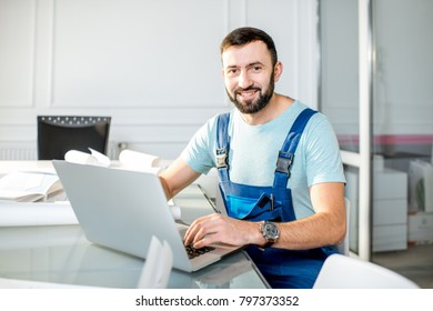 Handsome repairman or foreman in uniform working with laptop and architectural drawings at the office