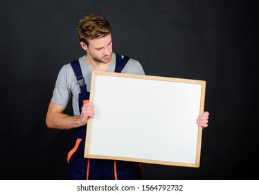 Handsome repairman. Man repairman builder work clothes. Plan repair work using blueprints or diagrams. Troubleshoot and fix faulty electrical switches. Repairman engineer hold whiteboard copy space.