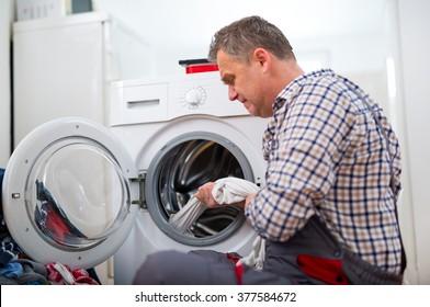 Handsome repairman repairing washing machine in kitchen