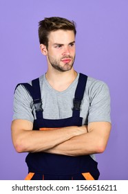 Handsome repairman. Worker violet background. Man repairman builder in work clothes. Troubleshoot and fix faulty electrical switches. Assemble and set up machinery or equipment. Thoughtful repairman.