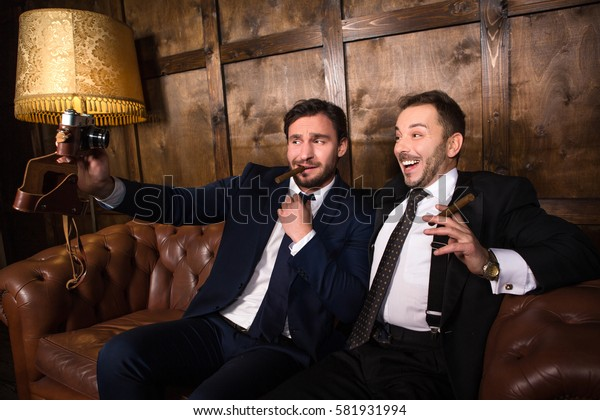 Handsome rich businessmen with cigars posing for camera. Two friends making self photos on smart camera in restaurant.