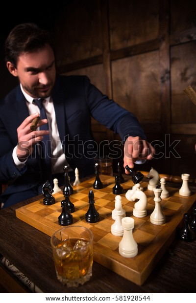 Handsome rich executive man playing chess and smoking expensive cigar. Glass with whiskey. Business concept. Restaurant atmosphere.