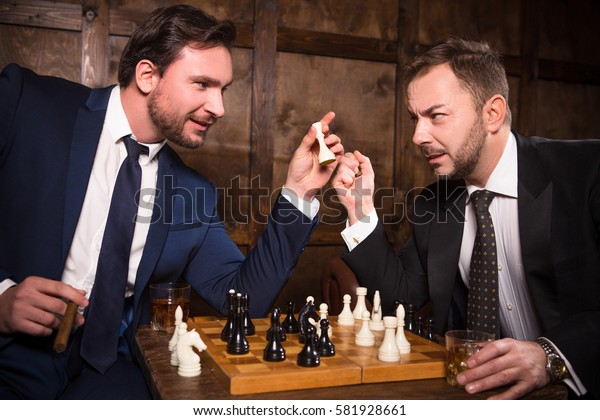 Handsome rich men playing chess all together in expensive restaurant or cafe. Rich men sitting face to face demonstrating competition between their enterprises, companies or firms.