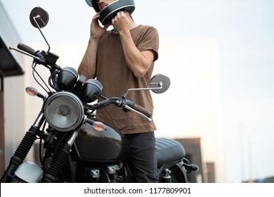 Handsome rider biker guy wearing black helmet and sitting on classic style cafe racer motorcycle. Bike custom made in vintage garage. Brutal fun urban lifestyle. Outdoor portrait.