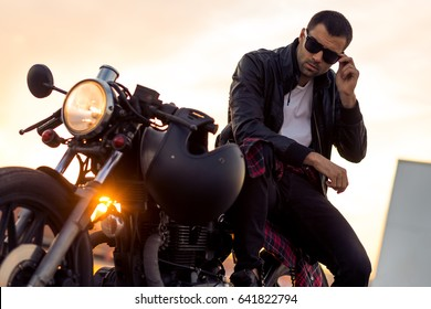 Handsome rider guy with beard and mustache in black biker jacket take off sunglasses on classic style cafe racer motorcycle at sunset. Bike custom made in vintage garage. Brutal fun urban lifestyle.