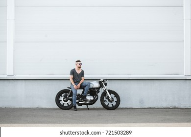 Handsome rider guy with beard and mustache sitting on classic style cafe racer motorcycle at day time. Bike custom made in vintage garage. Brutal urban lifestyle