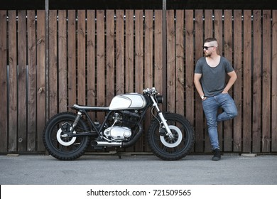 Handsome rider guy with beard and mustache standing next to classic style cafe racer motorcycle near wooden wall at day time . Bike custom made in vintage garage. Brutal fun urban lifestyle