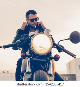 Handsome rider man with beard and mustache smoking cigaret and correct biker jacket sit on classic style cafe racer motorbike at sunset. Bike custom made in vintage garage. Brutal fun urban lifestyle.