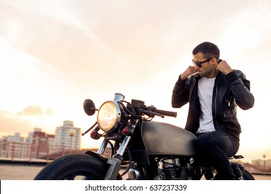 Handsome rider man with beard and mustache in black fashion sunglasses smoking cigaret and correct biker jacket sit on classic style cafe racer motorbike at sunset. Brutal fun urban lifestyle.