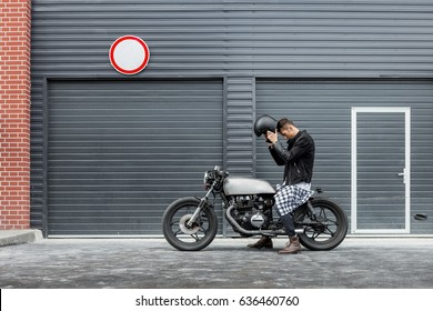 Handsome rider man put on black biker helmet while sit on classic style cafe racer motorcycle near industrial gates. Bike custom made in vintage garage. Brutal fun urban lifestyle. Outdoor portrait.