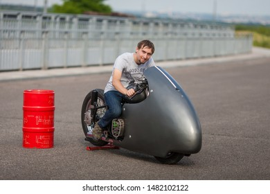 Handsome rider man sitting on classical race motorbike near barrel of oil on an open road. Brutal young man sitting at powerful shiny style cruiser motorbike on highway