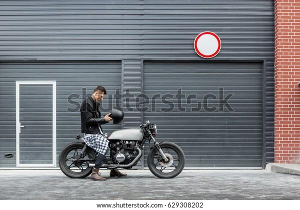 Handsome rider man take off black biker helmet while sit on classic style cafe racer motorcycle near industrial gates. Bike custom made in vintage garage. Brutal fun urban lifestyle. Outdoor portrait.