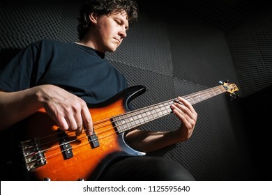 Handsome rock bass guitarist practicing in sound studio.