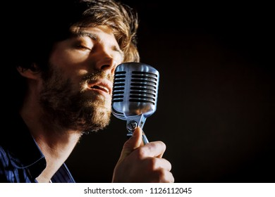 Handsome rock singer with retro microphone.